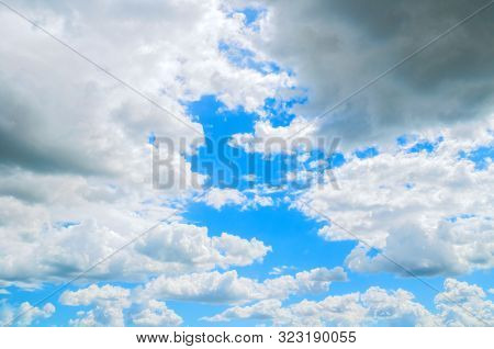 Dramatic blue sky background. Picturesque colorful clouds lit by sunlight. Vast sky landscape panoramic scene. Colorful summer sky view in bright tones