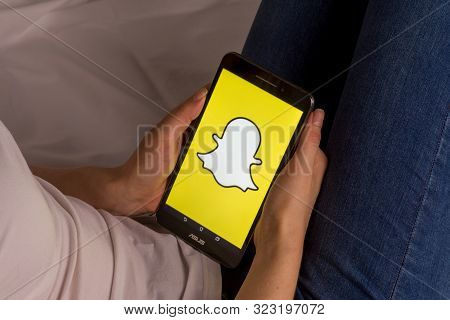 Tula, Russia, September 17, 2019: Asian Girl Lies On The Bed And Holds A Tablet With Snapchat Logo O