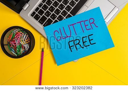 Word writing text Clutter Free. Business concept for Well organized and arranged Tidy All things in right places Trendy metallic laptop small paper sheet pencil clips colored background. poster