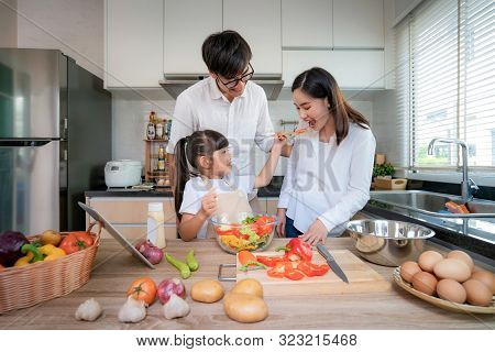 Asian Daughters Feeding Salad To Her Mother And Her Father Stand By When A Family Cooking In The Kit