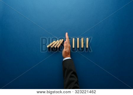 Top View  Of Businessman Hand Stopping Falling Dominos In A Business Crisis Management Conceptual Im