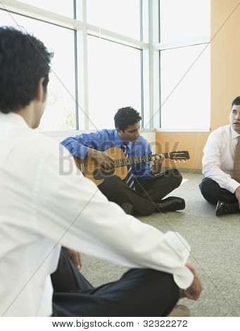 Businessman playing guitar with coworkers