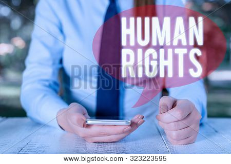 Writing note showing Huanalysis Rights. Business photo showcasing Moral Principles Standards Norms of a showing protected by Law Female business person sitting by table and holding mobile phone. poster
