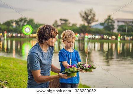 Father And Son Tourists Holds The Loy Krathong In Her Hands And Is About To Launch It Into The Water