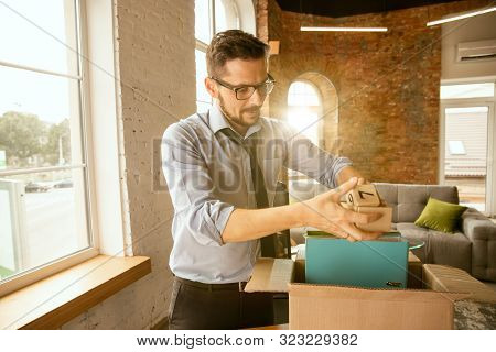 Young Businessman Fired, Looks Upset. Has To Pack His Office Belongings And To Leave Work Place For