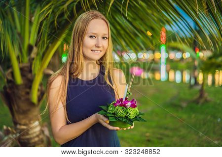 A Female Tourist Holds The Loy Krathong In Her Hands And Is About To Launch It Into The Water. Loy K