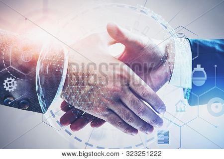 Close Up Of Two Businessmen Shaking Hands Over White Background With Double Exposure Of Planet Holog