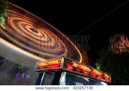 Round Ferris Wheel Spins Fast At Black Night. Neon Lights Beautifully Illuminate Ferris Wheel Which