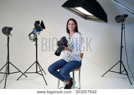 Portrait Of Female Photographer In Studio For Photo Shoot With Camera And Lighting Equipment