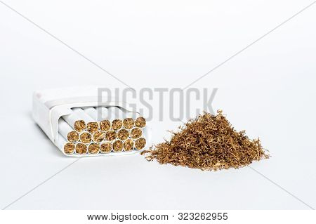 A Pile Of Natural Cigarette Tobacco Next To An Open Pack Of Cigarettes On A White Background.