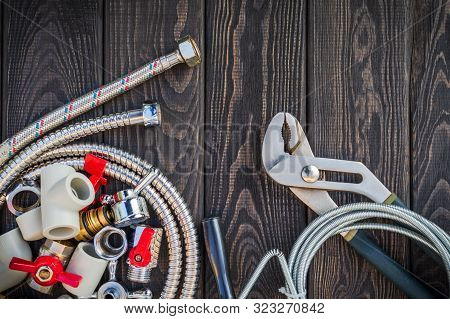 Necessary Set Of Tools And Spare Parts For Plumbers On Dark Vintage Wooden Background