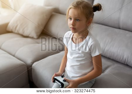 Enthusiastic kid in casual outfit playing with joystick while sitting on sofa in livingroom poster