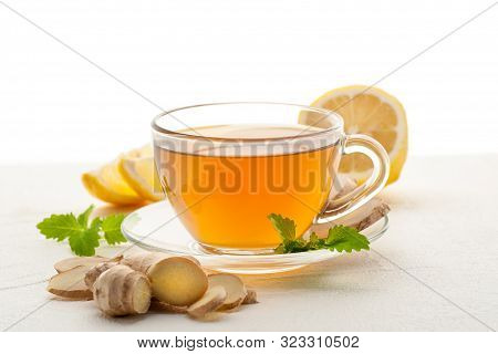 Ginger Tea In A Cup. Hot Drink With Lemon, Ginger And Mint On White Background. Close Up And Horizon