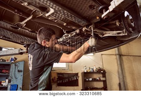Experienced Specialist Car Mechanic Standing Under Lifted Car During Repair And Maintenance Process