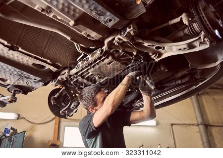 Repairman Fixing Car In Garage. Experienced Specialist Car Mechanic Standing Under Lifted Car During