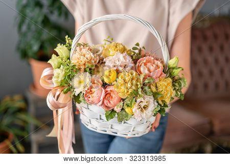 Flower Arrangement In Wicker Basket. Beautiful Bouquet Of Mixed Flowers In Woman Hand. Floral Shop C