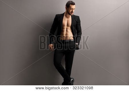 Handsome man in a black suit posing shirtless against a gray wall