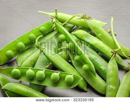 Green Pea Pod Table Peas. Closeup Of Fresh Green Peas (pisum Sativum) In A Glass Jar On A Wooden Tab