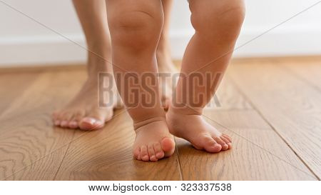 Close Up Of Mother Helping Baby Son To Take First Steps At Home
