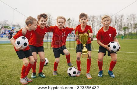 Happy Junior Sports Team. Young Boys In Soccer Team Holding Golden Cup And Soccer Balls. Group Of Ch