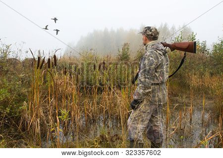 A Hunter With A Shotgun On His Shoulder Watches The Ducks Fly Away On A Foggy Morning