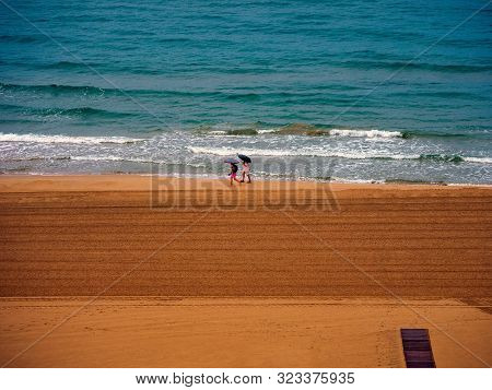 Two People Walking On The Beach Of Gandia In Valencia Spain On A Rainy Day