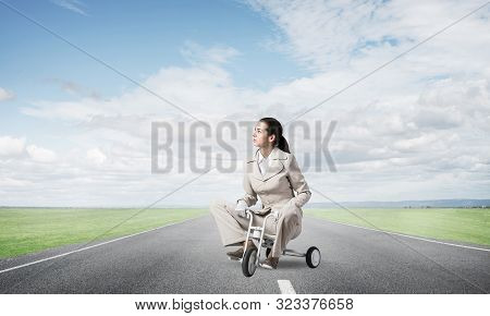 Caucasian woman riding kids bicycle on asphalt road. Young employee in white business suit biking outdoor. metaphor of ineffective and incompetent work. Beginner level concept with bicyclist. poster