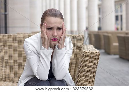 Young Woman With Headache Sits Outdoor In Cafe. Unhealthy Female In Pain. Sharp Strong Sore. Sad Bus