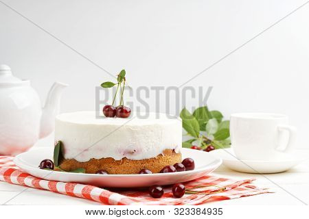 Homemade Cherry Pie With Delicate Yogurt Filling And Cup Of Tea On White Wooden Table
