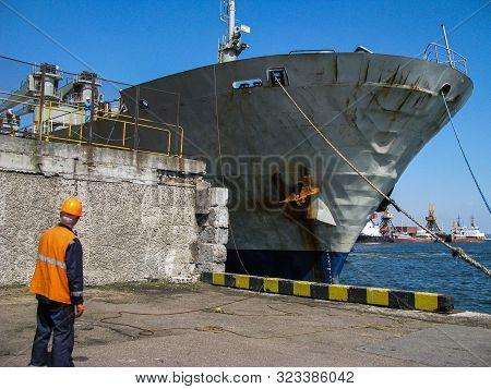 Mooring Moment Of A Bulk Carrier To The Berth. Sailor Mooring Awaits Mooring Rope