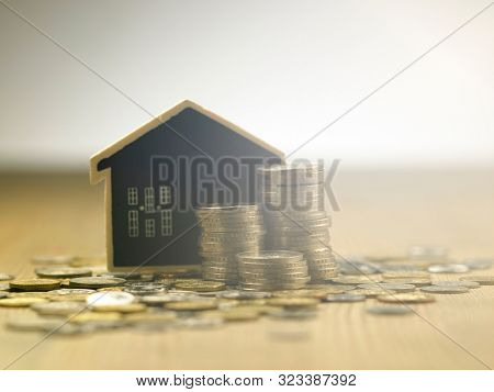 stacks of malaysia currency coin with blackboard model house focus on the foreground