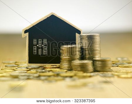 stacks of malaysia currency coin with blackboard model house focus on the background