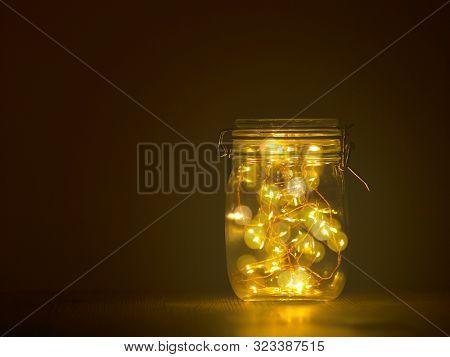 glass jar full of light on dark background