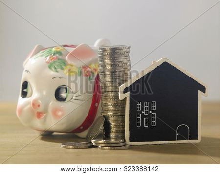 cute little baby piggy bank with stack of coins and model house