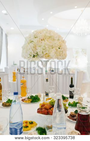 Composition Of White Artificial Flowers On A Glass Vase With A Long Leg On The Banquet Wedding Table