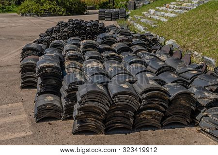 Stacks Of Black Ceramic Roofing Tiles Sitting On Concrete With Trees Of Public Park In Background.