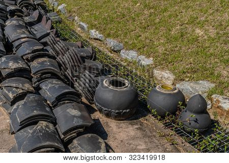 Stacks Of Black Ceramic Roofing Tiles Sitting On Concrete Next To Lawn In Public Park.