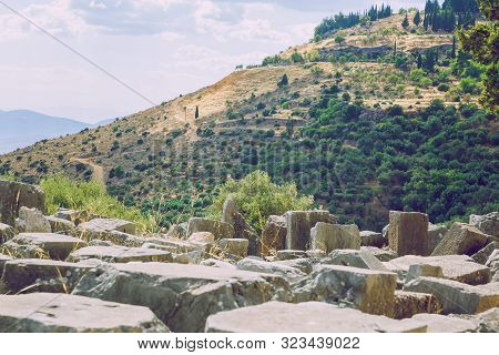 City Delphi. Greek Republic. Ancient Greek Ruins And Columns From Ancient Times.  Walking Tourists.