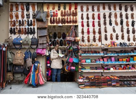 Florence,italy -  april 11, 2018: Unidentified Woman In Street Shop With Sandals, Handbags,caps