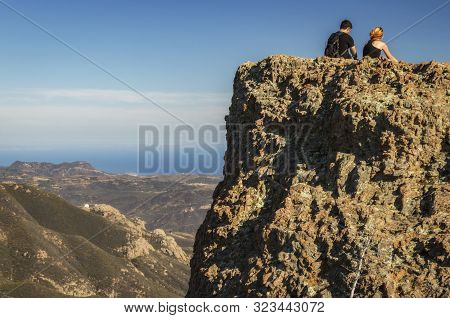 Two Hikers Overlook The Pacific Ocean From The Santa Monica Mountains In Southern California