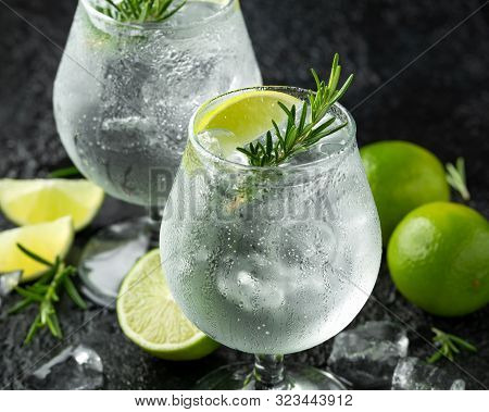 Gin And Tonic Alcohol Drink With Lime, Rosemary And Ice On Rustic Black Table