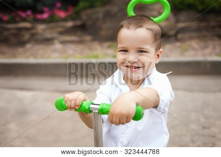 Adorable Small Child Boy Riding A Green Trike In The Park. Concept Of Happy Childhood