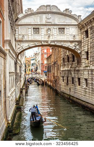 Gondola With Tourists Sails On Old Canal Under Medieval Bridge Of Sighs, Venice, Italy. Famous Histo