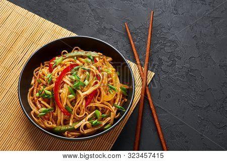 Vegetarian Schezwan Noodles Or Vegetable Hakka Noodles Or Chow Mein In Black Bowl At Dark Background