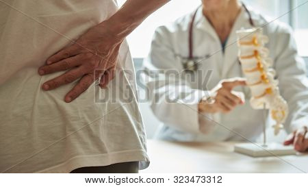 A Male Doctor Explaining Lumbar Anatomy To Female Patient Complaining Of Back Pain At Medical Clinic