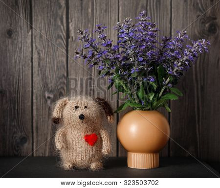 Cute Still Life With A Knitted Wool Dog And A Bouquet Of Purple Flowers On A Wooden Background. Vint