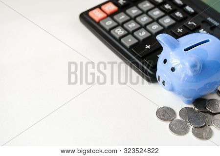 Blue Piggy Bank, Calculator And Coins On White Background With Copy Space. The Concept Of Budgeting.