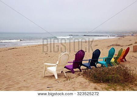 Colorful Plastic Adirondack Chairs Are Set Out On The Beach Ready For Occupancy.