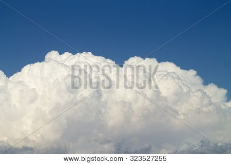 White and gray puffy cumulus clouds in the bright blue sky poster