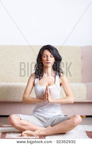 Portrait of young happy woman doing yoga exercise at home